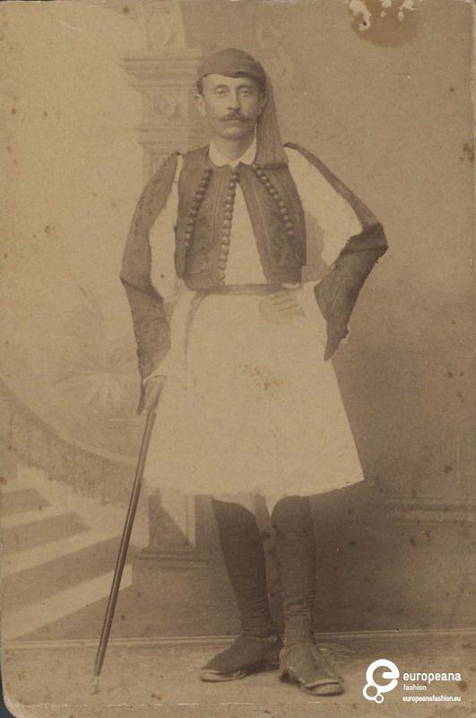 "B/W photo of a man in fustanela costume. Inscriptions: ""Π.Μωραϊτης, ΦΩΤΟΓΡΑΦΟΣ ΤΗΣ ΒΑΣΙΛΙΚΗΣ ΟΙΚΟΓΕΝΕΙΑΣ, 82, Οδός Αιόλου, ΑΘΗΝΑΙ"", ""P.Moraites & Co - PHOTOGRAPHES DE LA FAMILLE ROYALE, 82 Rue d'Ecole, ATHENES"",  ""θανάτου το '901"".Date: 1880. Institution: Peloponnesian Folklore Foundation Provider: Europeana Fashion"
