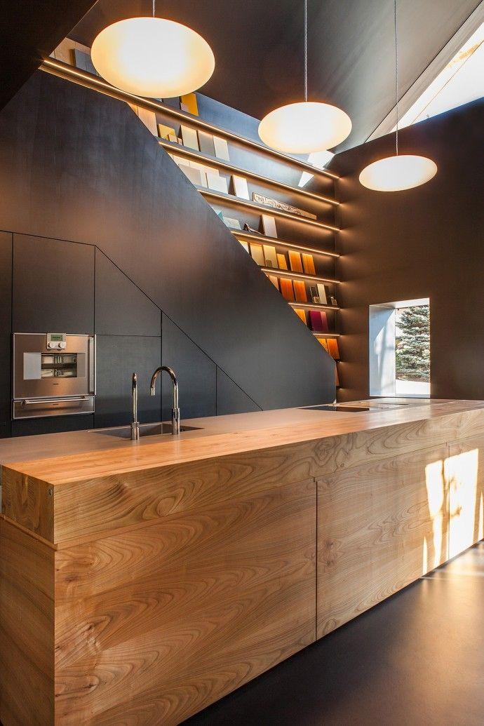 Fantastique et minimaliste, cette cuisine où tous les éléments sont intégrés s'impose dans le salon sous la forme d'un grand comptoir en bois massif.