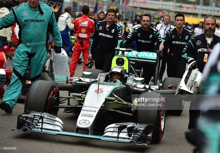 Pit crew members push the car of Mercedes AMG Petronas F1 Team's German driver Nico Rosberg to his position on the grid before the start of the Russian Formula One Grand Prix at the Sochi Autodrom circuit in Sochi on October 11, 2015. AFP PHOTO / ANDREJ ISAKOVIC