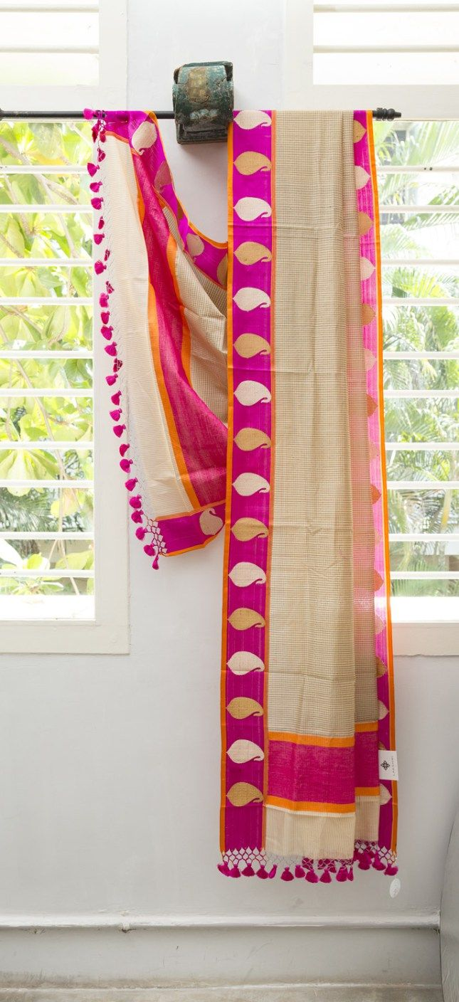 This beige Benares cotton has black thread work forming fine checks throughout. The border is a magenta band with gold and silver zari motifs running along it, with an orange selvedge. The pallu ha…