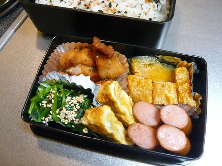 The bottom okazu half has fried chicken pieces, boiled pumpkin, sausages, omelet, and blanched spinach with sesame seeds