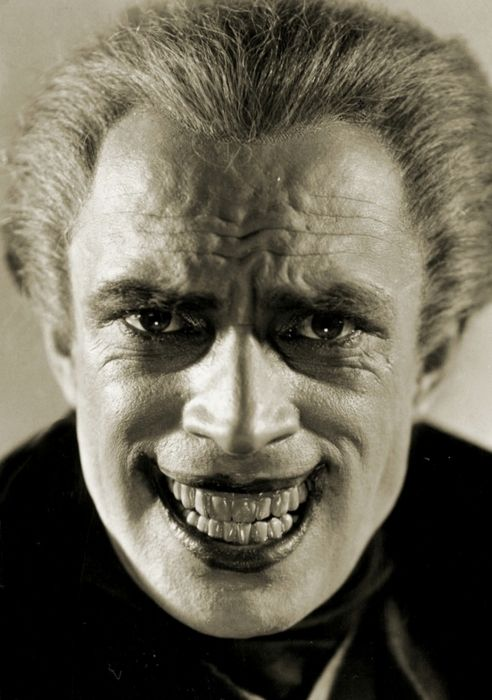 """Conrad Veidt, in an early version of his make-up for his character in The Man Who Laughs (1928), who later served as the inspiration for The Joker.The permanent grin was achieved by drawing back the corners of his mouth with hooks attached to the sides of his dentures.  """"Paul Leni, who made Waxworks, the cause of my coming to Hollywood, was the director of my picture, The Man Who Laughs, and we were all very happy about it. It was the Victor Hugo story of the man whose lips were cut away"""