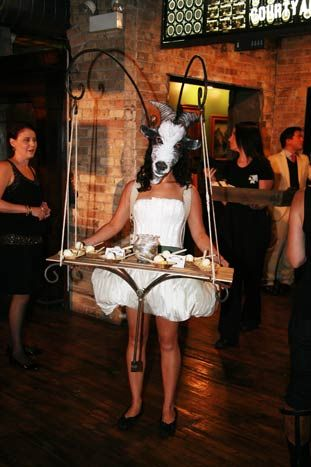 Stephanie Izard, who is behind popular restaurant Girl and the Goat, released her book Girl in the Kitchen in Chicago in 2011. Kicking off her book tour was a farmers'-market-theme party with surreal touches—like a Redmoon performer in a goat's mask serving desserts from a tray attached to her middle.  Photo: Rita Shimelfarb/Polaris Productions