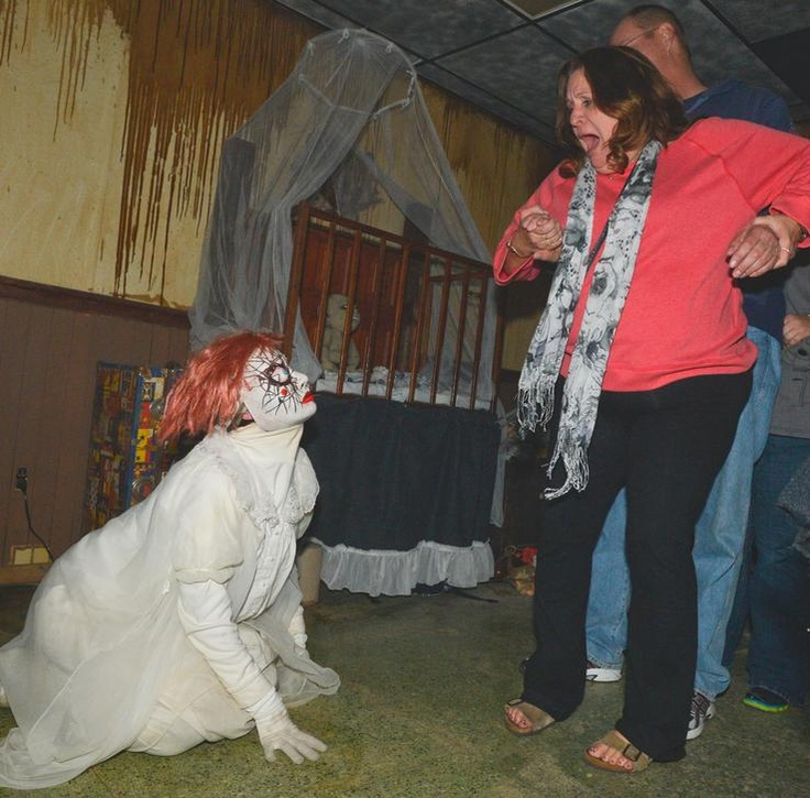 Deanna Lawson, left, dressed as a crazed doll, puts a scare into Kathleen Deffenbaugh while husband Allen Deffenbaugh holds on to her during a walk through the Haunted Infirmary at Bartonville Insane Asylum on Friday. The Limestone JFL and Friends operate the haunted house in October through Halloween.