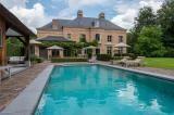 Aan de achterzijde van de villa bevinden zich ruime terrassen alsook een verwarmd buitenzwembad met automatisch roldek, een poolhouse met sanitair en kleedruimte. In het poolhouse bevindt zich tevens een berging met technische ruimte voor het zwembad.