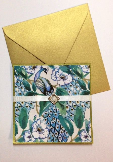 This beautiful invitation makes the perfect introduction to a wedding, formal or social function. The invitation is made using a metallic moss green card. The peacock palace patterned paper makes up the front and a bridal white double faced satin ribbon with diamond shaped rhinestone buckle forms a sash enclosure. Inside the card sits the printed invitation on marshmallow crisp white matte paper. Materials available from OccasionalPapers.com.au