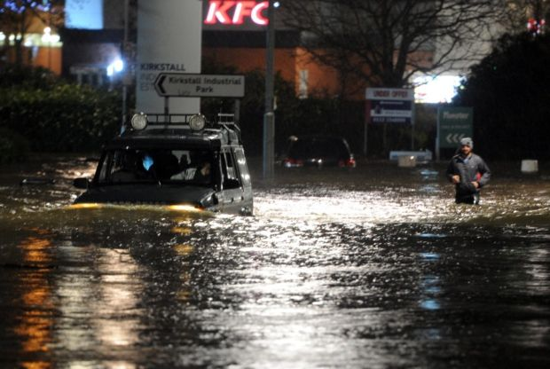 Car and pedestrian make wsy through floodwater on Kirkstall Road in Leeds after the River Aire burst its banks.  (Picture Tony Johnson)