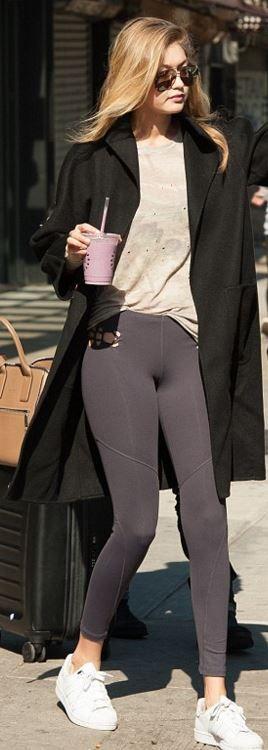 Who made  Gigi Hadid's black aviator sunglasses, gray tee, white sneakers, and tan handbag?
