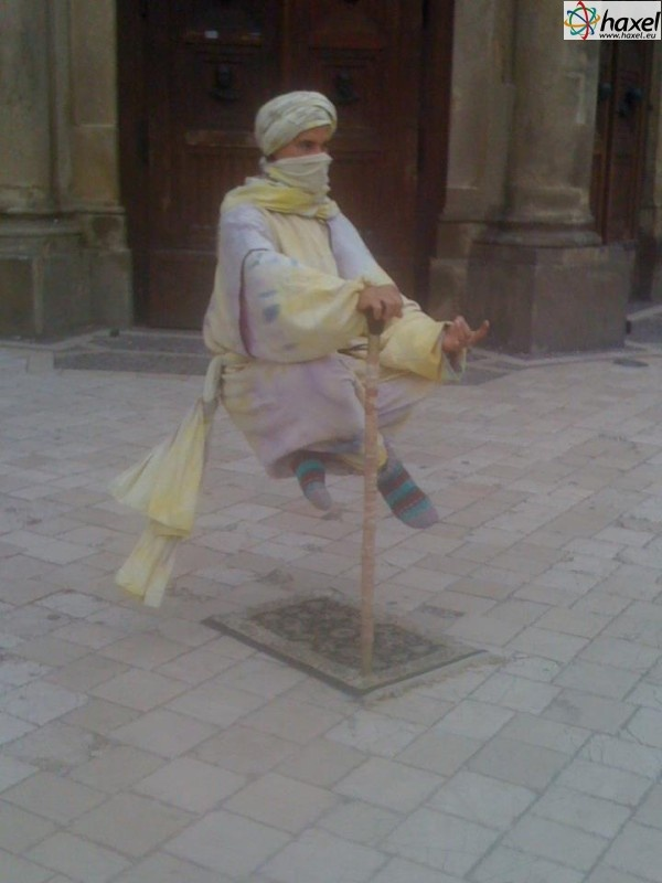 "Magician ""levitating"" in front of the famous Mary's Basilica on the Main Market Square in Cracow"