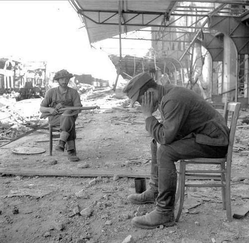 A Canadian soldier guards a captured German soldier.