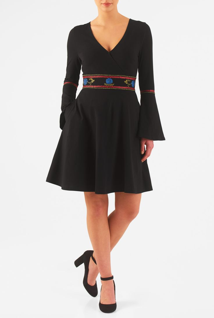 Our surplice cotton knit dress with embellishment at the banded waist and elbows flows gracefully down to the flounced cuffs and flared skirt.