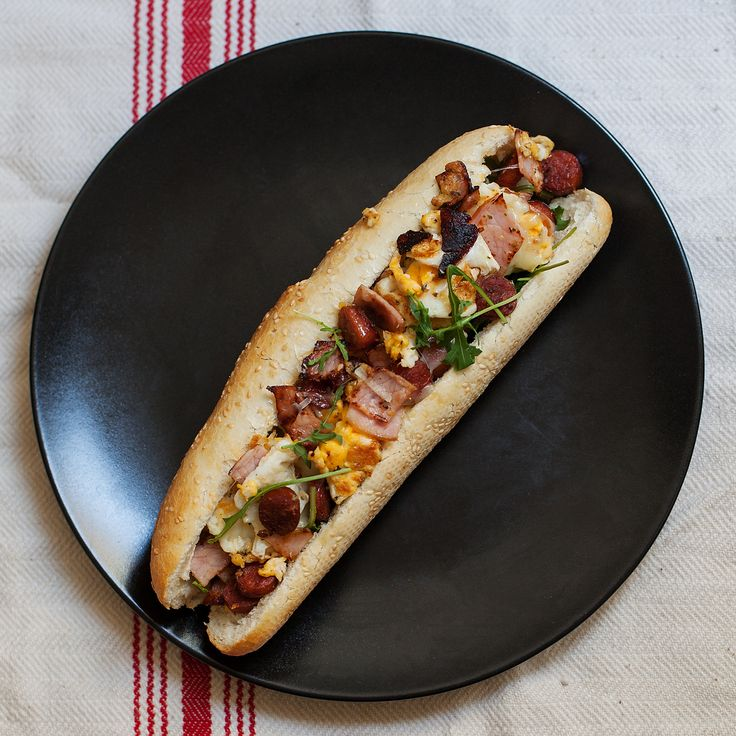Breakfast sandwich. Sausage, ham, eggs, mayo, horseradish paste, herbs, cream cheese, cheese, arugula, bread.