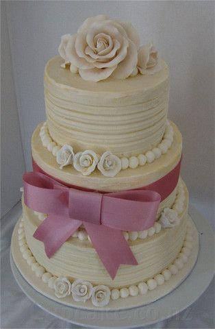 Cream wedding cake with pink bow