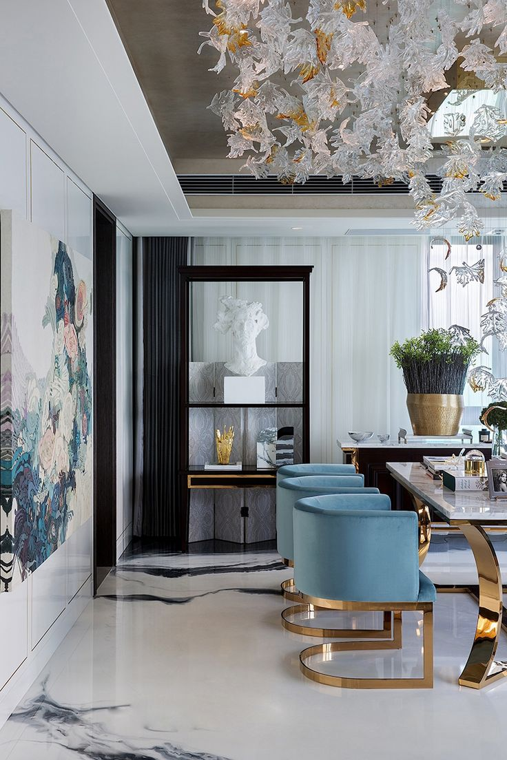 Gorgeous room! Blue and gold velvet chairs, ceiling sculpture, oversized art