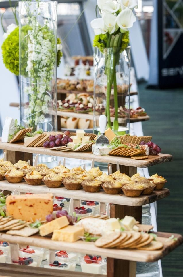 Food display with local fresh cheeses, pastries, crackers and fresh flower displays. #eventdesign #catering #foodbuffets