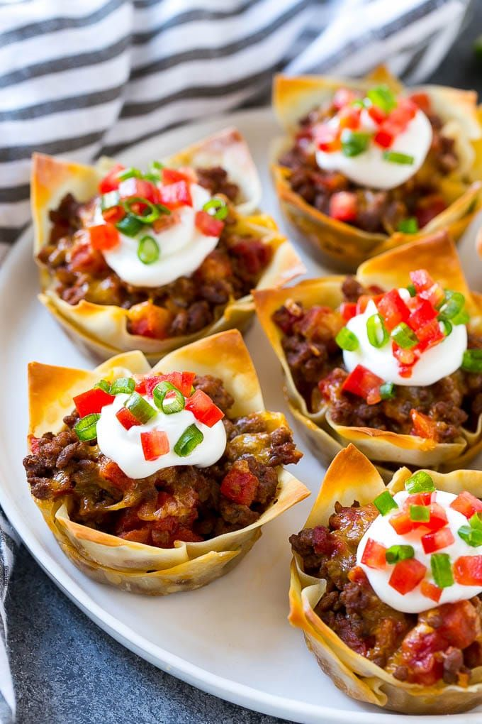 These wonton taco cups are the perfect appetizer or fun twist on taco night! Layers of seasoned beef and cheese are baked in layers of wontons in a cupcake pan, then finished off with your favorite taco toppings.