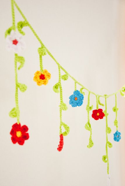 Flower Garland by mo + me, via Flickr - SAVE your chain(s) that you learned to crochet with. When you learn just a little more - you can add flowers (or butterflies, whatever) and make a beautiful garland!