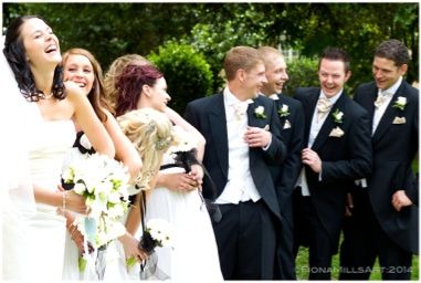Candid moment of bridal party laughing as the pose for photos outside the church. Summer wedding day. Bride and groom giggling with bridesmaids, best man and ushers. Monochrome colour palate. Bridal style, ivory sating wedding dress, curled up do medium length wedding hair & veil. Natural makeup by benefit. Bridesmaids dresses in black and white, curled bridesmaids hair, white bouquet, flower posey. Black suit and tails, cream waistcoat and crevattes.