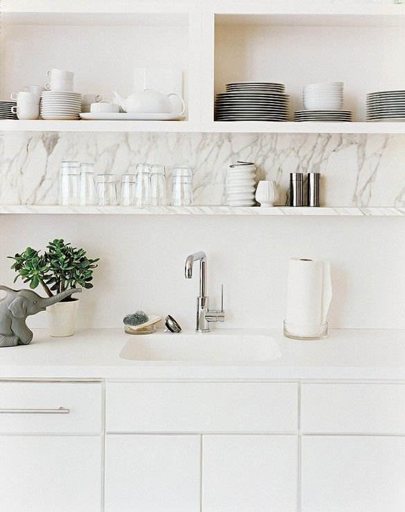 Bright white kitchen with open shelves and contemporary faucet.