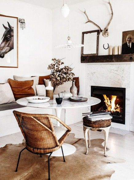 cozy dining space; rattan dining chair; saarinen dining table; marble fireplace surround; horse photo; antlers