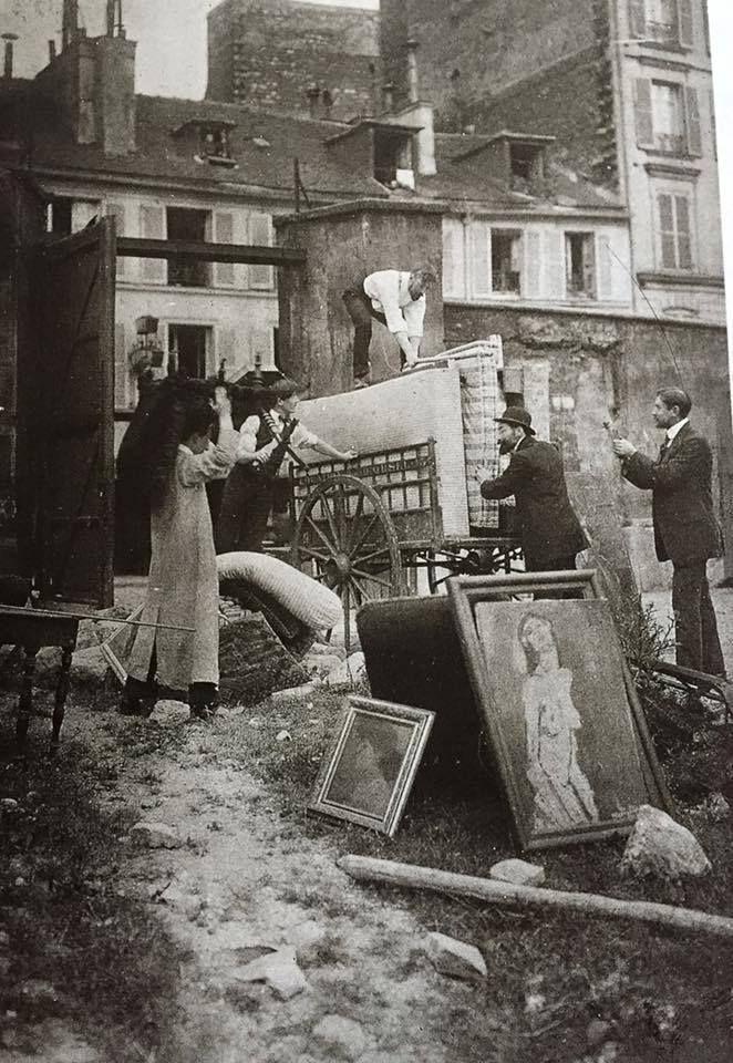 """Parigi. 5 luglio 1913. Amedeo Modigliani trasloca da rue du Delta a place Dancourt. Jean Dupont con la poltrona in testa , Henri Gazan, Paul Alexandre sul carretto, De Saint-Albin e De Val De Guymont. A terra dipinti di Modì, tra cui il famosissimo """"nudo dolente""""."""