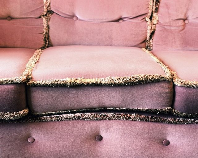 pink couch with gold fringe trim