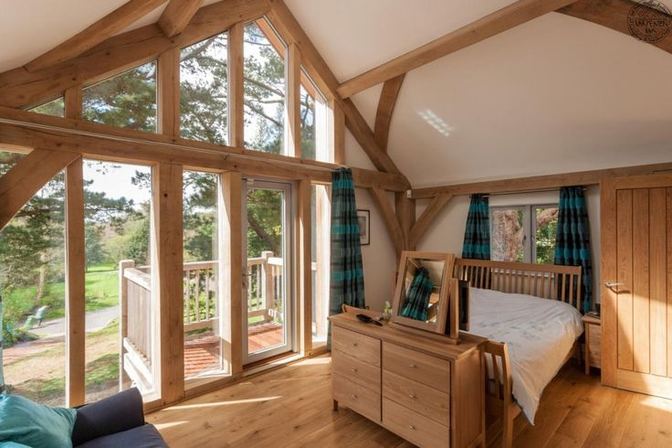 Amazing bedroom open to the rafters with fully glazed oak gable by Roderick James Architects.