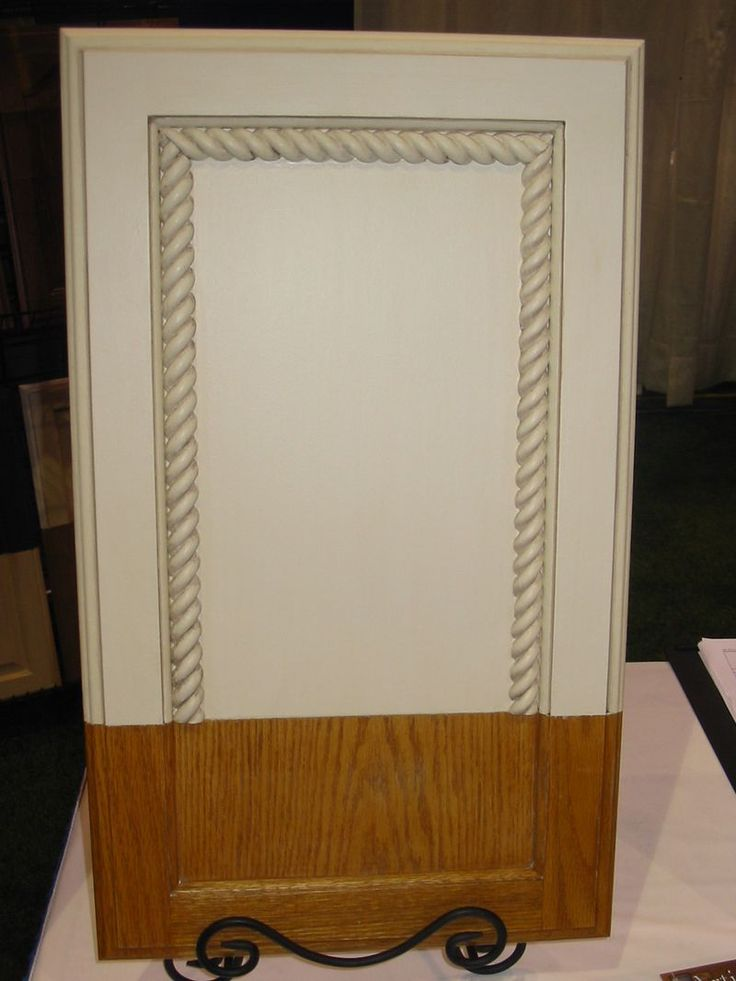 Transform standard builder grade cabinets into custom with the addition of rope molding, paint & glaze (and maybe a little crown molding on top) - the blog doesn't tell you how to do it, but with Pinterest, it shouldn't be hard to find out...