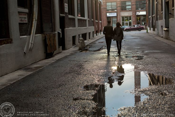 Reflection of a couple in a puddle as they walk away. Toronto Leslieville Engagement Photos #sweetheartempirephotography