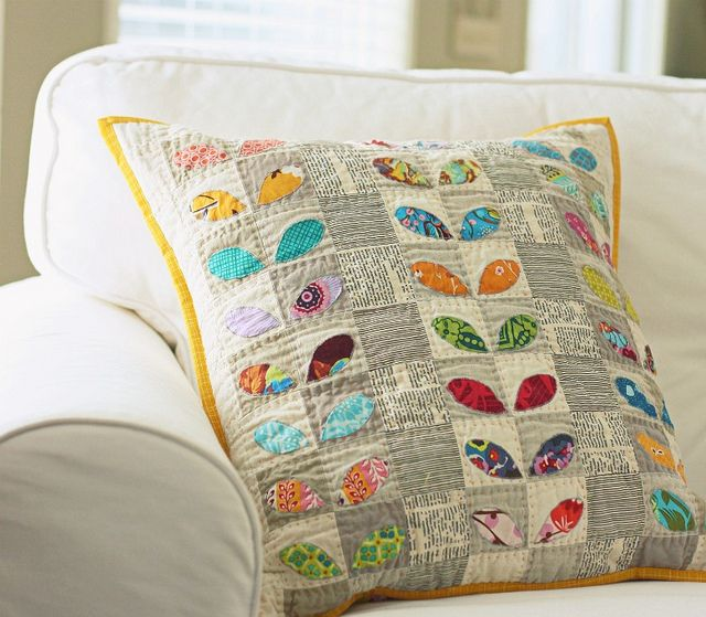 Pretty patchwork pillow on a white sofa. I especially like the use of grey squares & the bright yellow edging. I also love that some of the white squares appear to contain script.