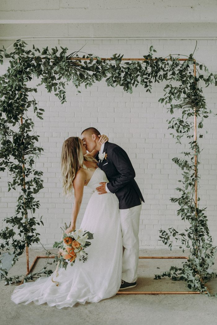 Gorgeous floral wedding ceremony arch with minimal decor, white brick and Italian ruscus garlands | image by Autumn Berrier #SeptemberWeddingIdeas