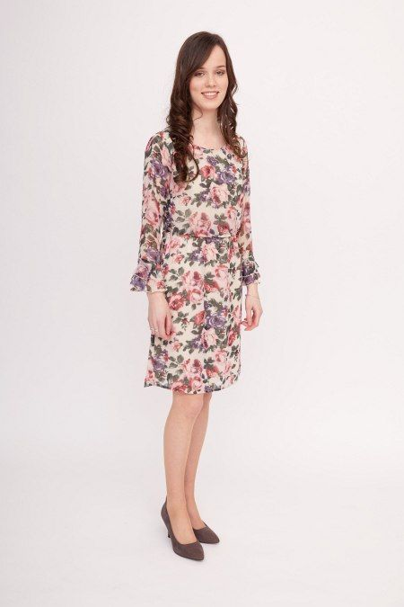 Dit jurkje met rozenprint is een vrolijke mix van rode, roze, blauwe en groene tinten. Het jurkje heeft een ronde hals en een elastieken ceintuur rond de taille die in de stof is verwerkt.