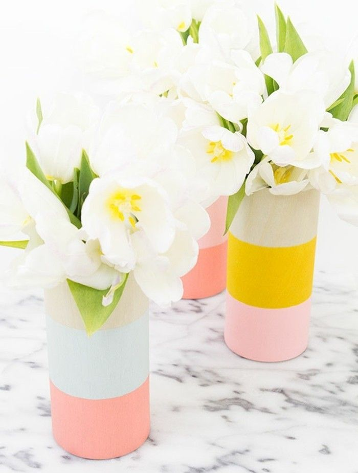flower vases painted in pastel pink, pale blue and vivid yellow, a set of three, placed on marble surface, and containing white tulips