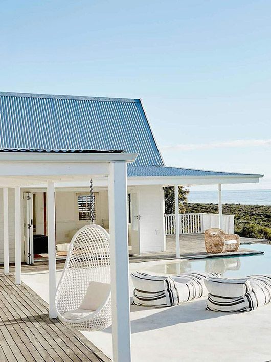 oh hello dreamy pool with farmhouse inspired beachiness AND hanging chairs AND cute striped loungers. the dream.