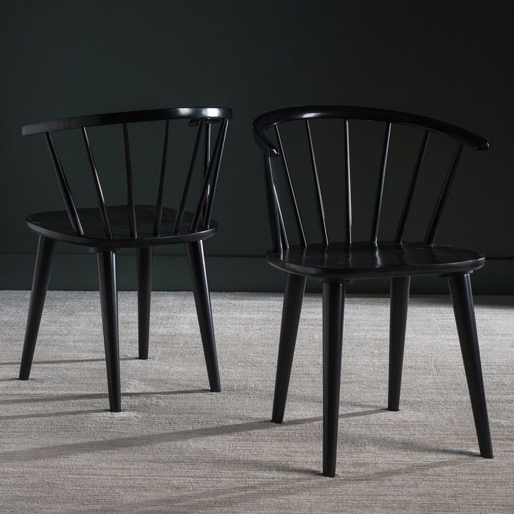 Inspired by the graceful curves of an antique captain's chair, this set of two dining chairs is crafted of sustainable rubber wood and finished in black.