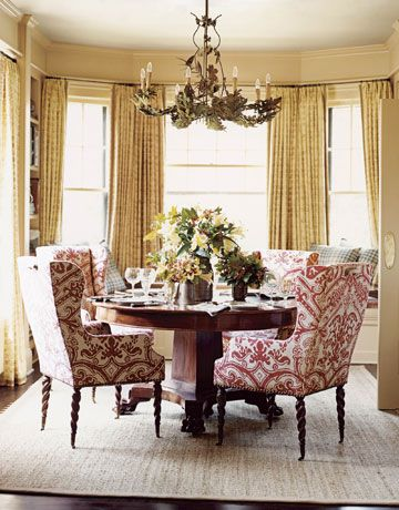 Round antique dining table with comfy wing chairs designed by Nancy Boszhardt, Courtesy House Beautiful