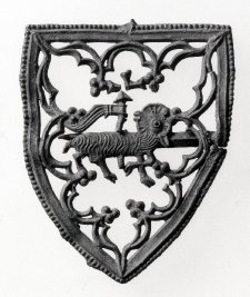 Pilgrim badge; lead alloy; brooch; frame in form of shield with beaded border, enclosing Agnus Dei and delicate openwork tracery; pin at back.