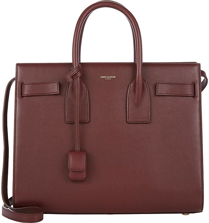 Saint Laurent SAINT LAURENT WOMEN'S SMALL SAC DE JOUR. Saint Laurent smooth bordeaux box calfskin small Sac De Jour Carryall. Leather tabs thread through side gussets and snap at bag front and back, gold-stamped logo at top line; polished goldtone protective metal feet and hardware Two-compartment interior lined with supple bordeaux suede; compartment-dividing pocket with two-way-zip, additional zip pocket and two slip pockets at interior Topstitched rolled top handles