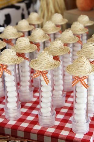 Tubos com guloseimas incrementados com chapéu de palha dão um toque a mais à mesa da festa Fazendinha