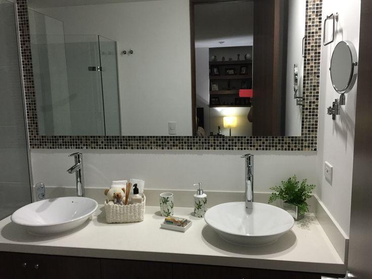 Baño con doble lavamanos y espejo con cenefa y d talles de decoración que le dan un toque muy acogedor.