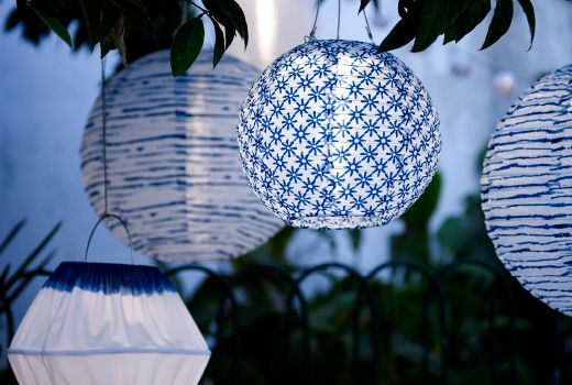 Several blue/white LED solar-powered pendant lamps in different shapes and sizes hanging in a tree.