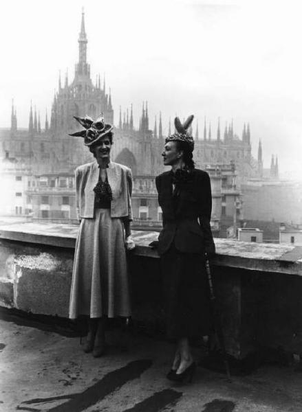 Fotografia di moda: due modelle in posa. Sullo sfondo, il Duomo. Milano (MI), Italia, 1945
