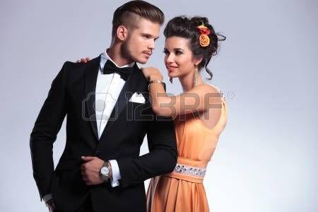 giovane coppia di moda con la donna dietro l'uomo appoggiato le mani sulle spalle, mentre lo guardava. su sfondo grigio Archivio Fotografico