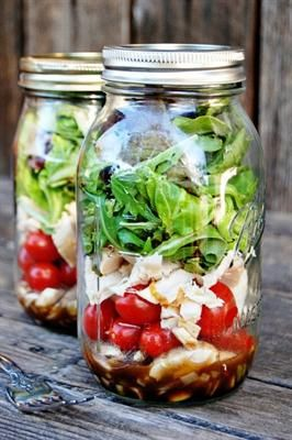 Layered salad in a mason jar: Lettuce, cherry tomato, meat, vinaigrette, chicken, mixed greens, gluten free