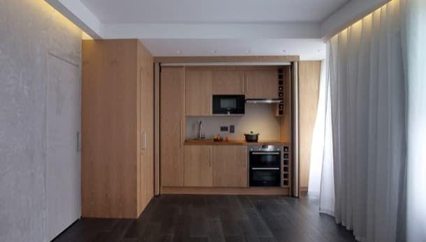 Micro apartamento para un artista. Spheron Architects realizó un gran trabajo en la reforma de un piso londinense con baño y cocina. Creó un moderno micro apartamento con puertas ocultas. La del baño está camuflada con los armarios de madera de la cocina. La puerta de acceso tiene la misma textura que la pared del estudio. Esta habitación dispone de toda una pared de vidrio espejo que oculta una cama abatible y armarios. El mobiliario es mínimo, solo hay una mesa y un