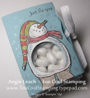 "Snow Much Fun Tic Tac Holder The base of the holder is created with a Two Tags die-cut tied up with a Whisper White Stitched Grosgrain Ribbon.  I colored one of the snowman images from Snow Much Fun using Blender Pens and Ink Pads.  After I cut out the colored image, I adhered it to the holder then punched out his tummy with the 1"" Circle Punch."