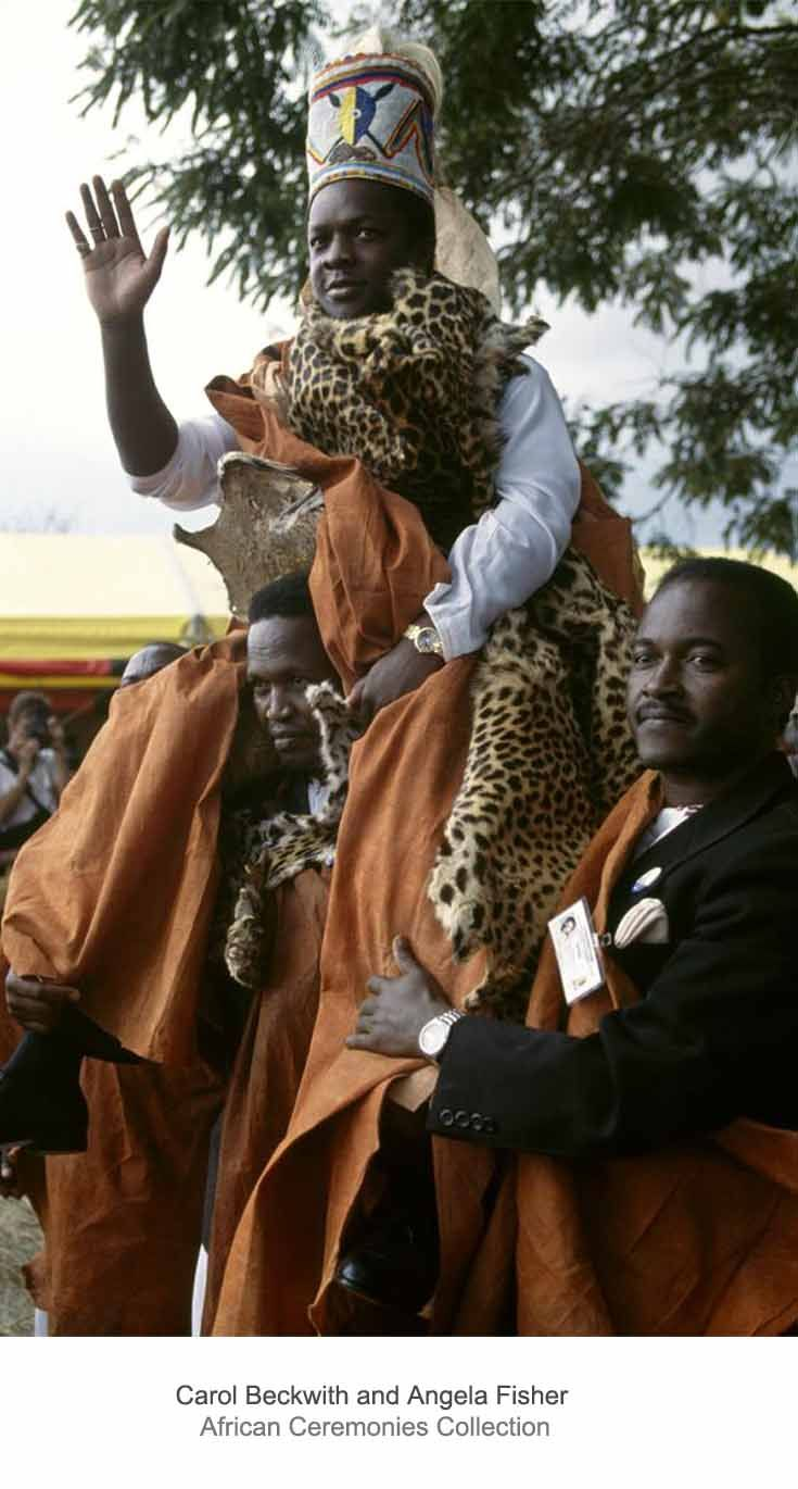 "Africa | The King of Buganda, Mutebi II, is carried by men from the Buffalo Clan, his traditional bearers, and shown to his people.  To the cheering of some 20'000 Baganda, who cried out ""Wangaala Kabaka"" (Long Live the King), the king greeted his subjects to the pounding of giant drums and shrill ululations of women.  Uganda. 