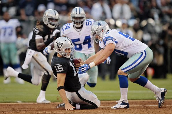 Sean Lee Photos Photos - Quarterback Matt Flynn of the Oakland Raiders slides after getting flushed out of the pocket by the Dallas Cowboys in the first quarter of a preseason game on August 9, 2013 at O.co Coliseum in Oakland, California. - Dallas Cowboys v Oakland Raiders