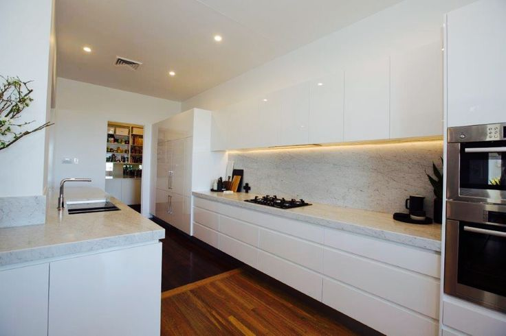 Bianco Carrara marble kitchen tops and splash back, 2 PAC polar white cabinetry with fully integrated refrigerators.