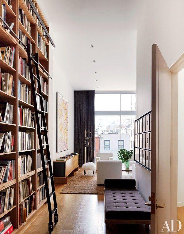 Floor-to-ceiling oak bookshelves distinguish the library | archdigest.com